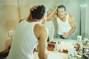 Парень смотрит в зеркало